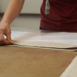 Conservator strip lining painting on canvas