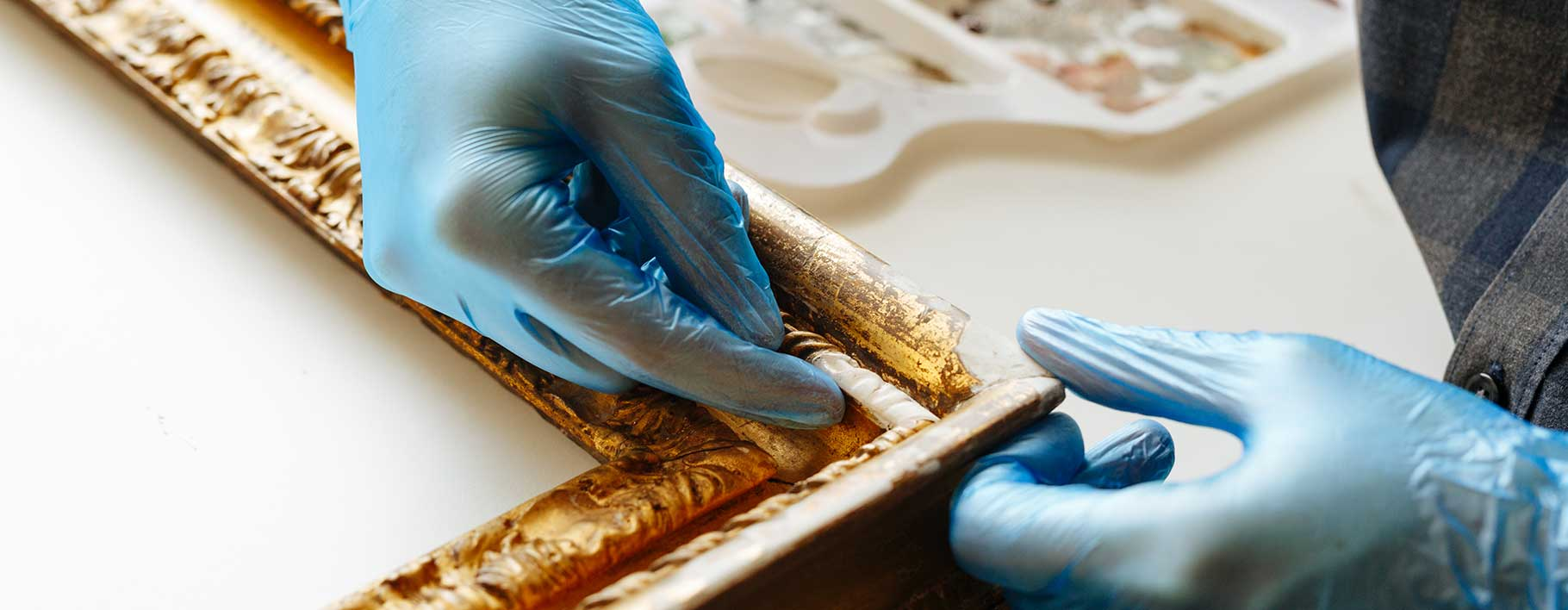 Conservator adding moulding to a picture frame