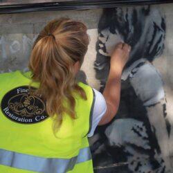 Martha restoring Extinction Rebellion Banksy at Marble Arch, London