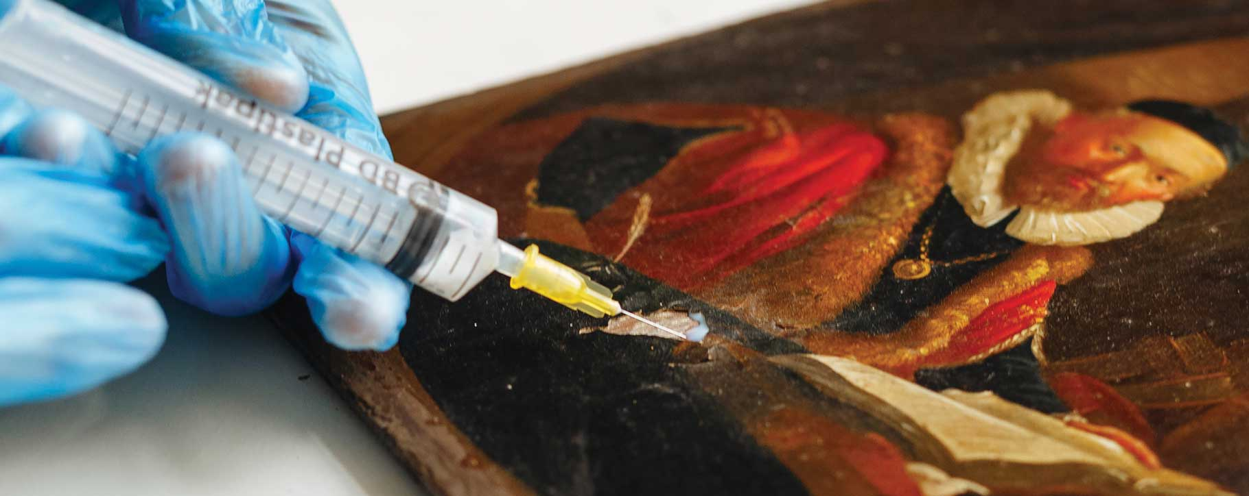 Injecting adhesive to re-adhere flaking paint