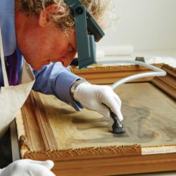 Conservator vaccuumming dust on painting