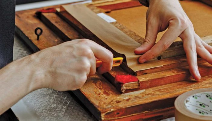 Applying tape to newly framed oil painting