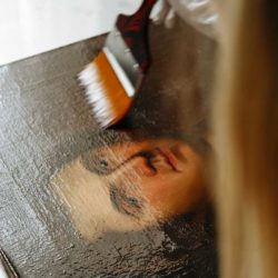 Applying varnish to oil painting portrait of a man