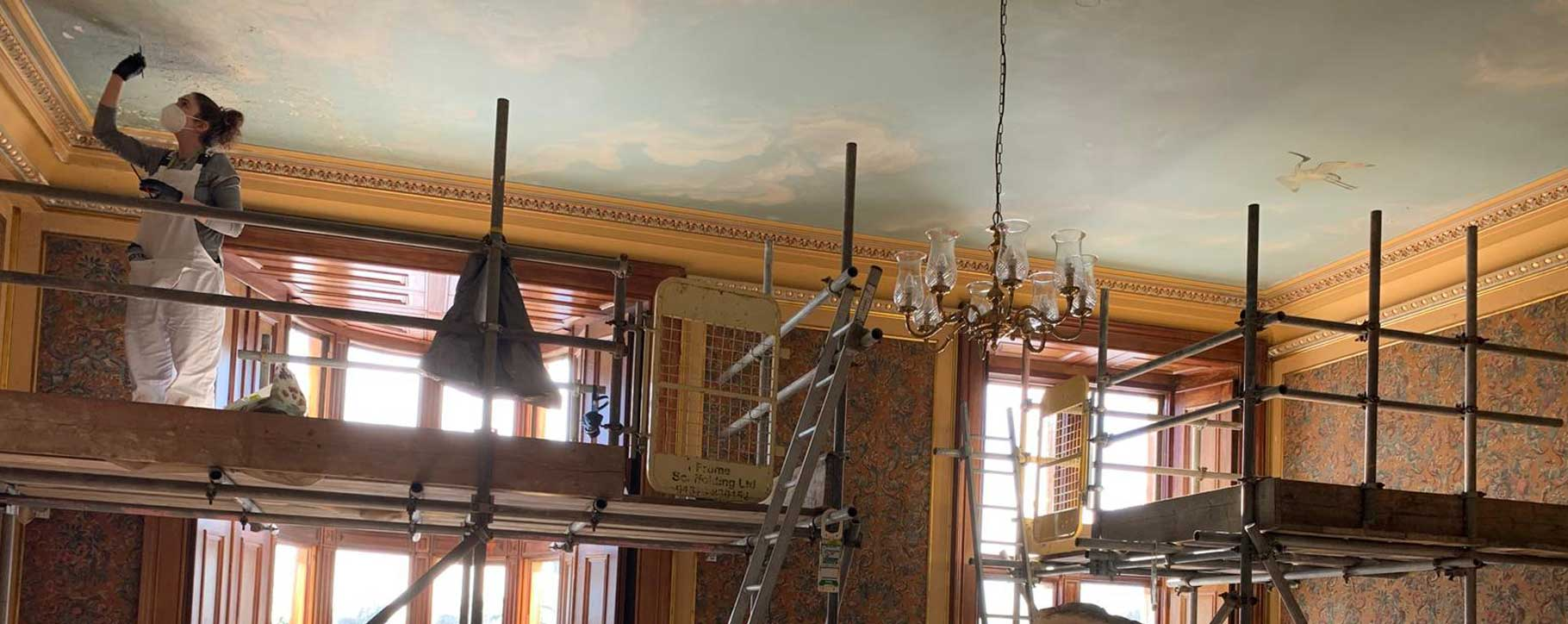 conservator working on westonbirt school ceiling restoration