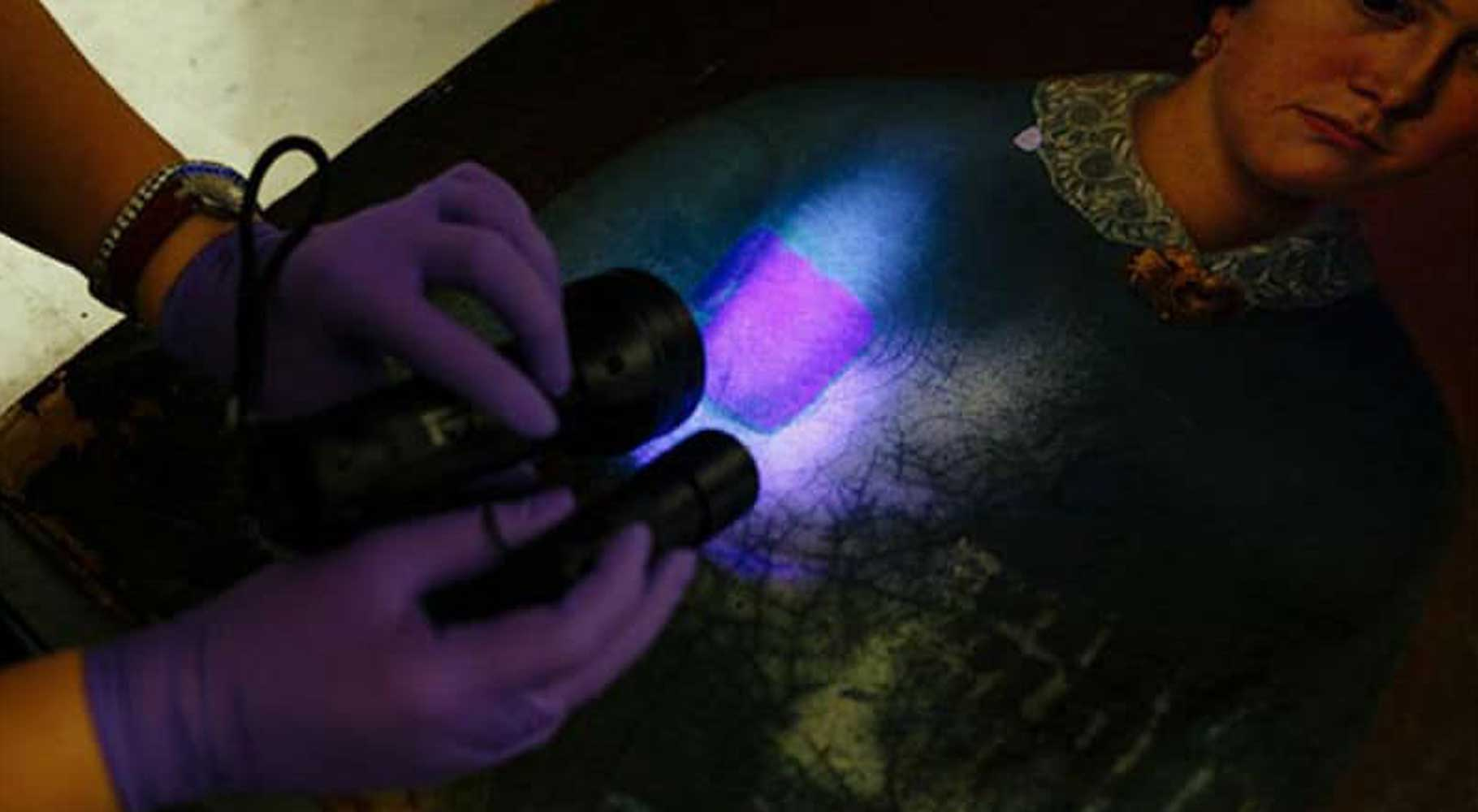 inspecting oil painting under uv light for hidden features